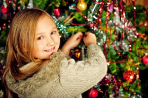 Girl removing ornament from tree